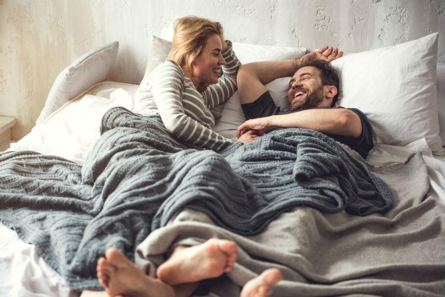 Fantasie sessuali: nell'immagine una donna e un uomo parlano a letto sorridendo