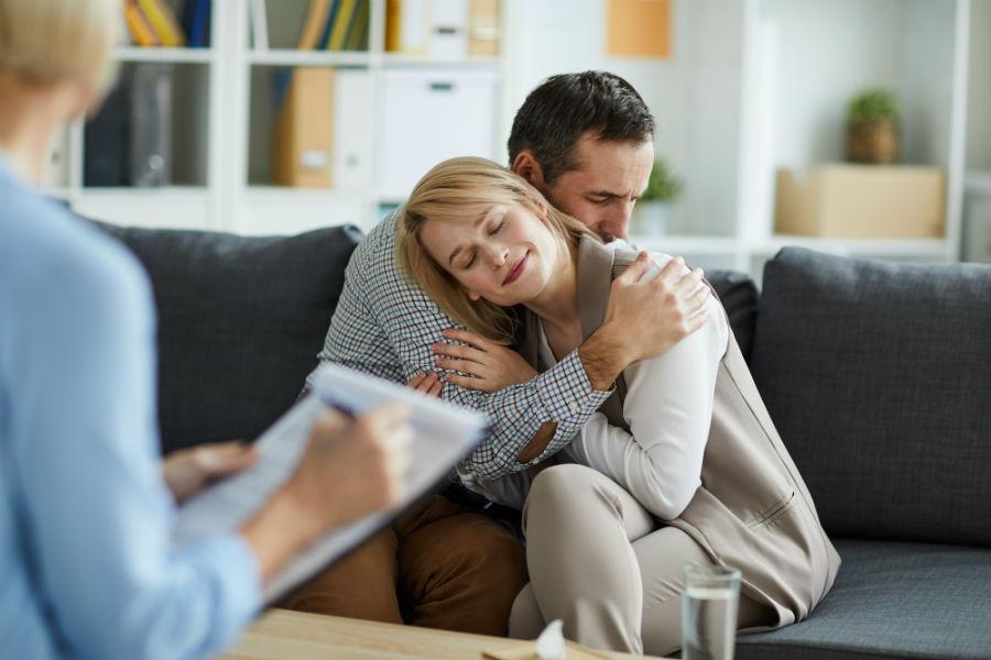 coppia si abbraccia seduta sul divano di uno psicoterapeuta